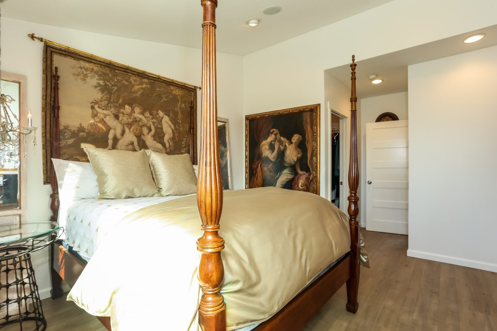 bedroom with 4 post bed and paintings on wall